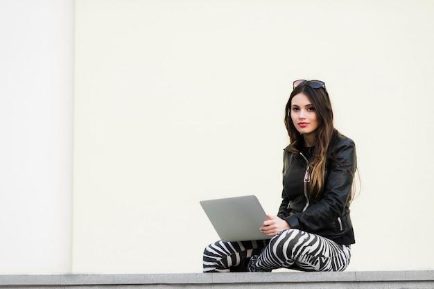 Mulher bela estudante está sorrindo usando um laptop e sentado na parede velha no campus da universidade. mulher linda, trabalhando com o computador ao ar livre no parque da faculdade. Foto Premium