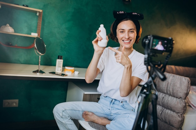 Mulher beleza vlogger filmando vlog sobre cremes Foto gratuita