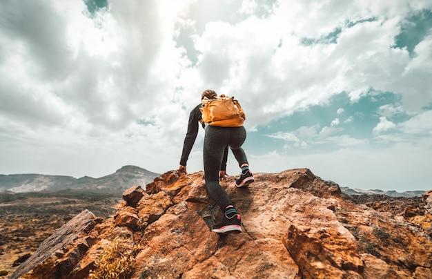 Mulher bem sucedida alpinista com mochila no topo da montanha, olhando o horizonte. Foto Premium