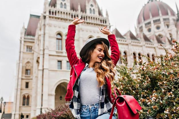 Mulher bem torneada em roupa de rua da moda expressando energia e curtindo um passeio pela parte antiga da cidade Foto gratuita