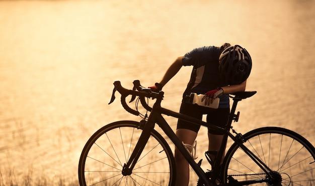 Mulher bicicleta de exercício ela se sentia cansado e relaxante bebida no rio Foto Premium