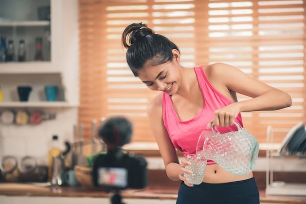 Mulher blogueira asiática fazer vlog como dieta e perda de peso, jovem fêmea usando gravação de câmera Foto gratuita