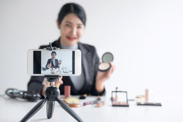 Mulher blogueira está apresentando tutorial beleza produto cosmético e transmissão de vídeo ao vivo Foto Premium