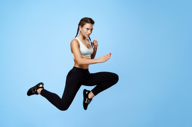 Mulher boa aptidão motivado no sportswear elegante legal, pulando alto com as mãos para cima, olhando para longe Foto gratuita
