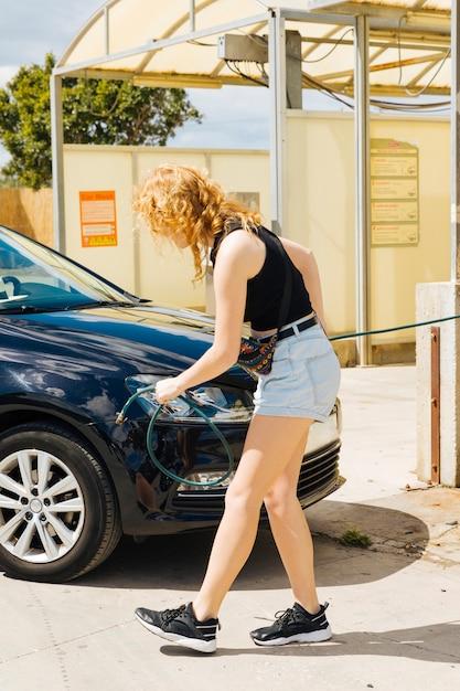 Mulher, bombear, cima, pneu, de, car, em, posto gasolina Foto gratuita