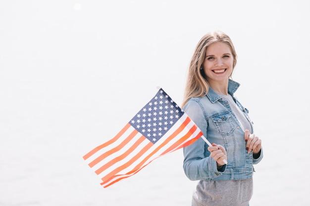 Mulher bonita, acenando a bandeira do eua na vara Foto gratuita