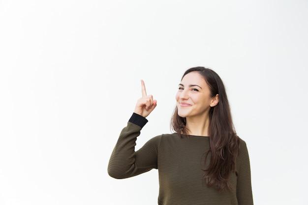 Mulher bonita alegre feliz apontando o dedo para cima Foto gratuita