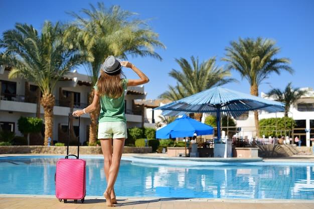 Mulher bonita andando perto da área da piscina do hotel com mala rosa Foto Premium