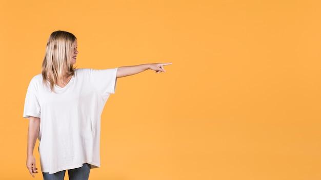 Mulher bonita, apontando ao lado de pé contra o pano de fundo amarelo Foto gratuita