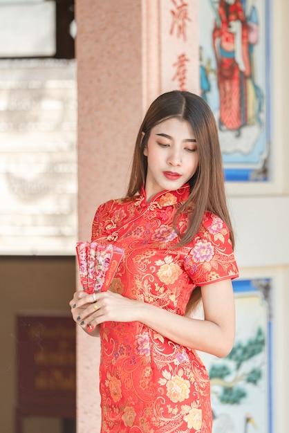 Mulher bonita asiática com vestido vermelho no ano novo chinês Foto Premium