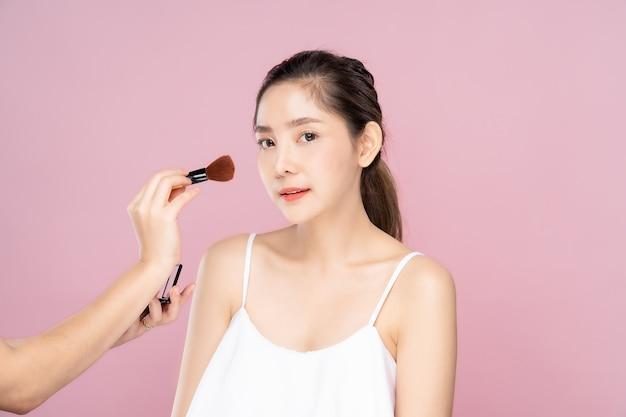 Mulher bonita asiática em pé com uma maquiagem por outra maquiagem menina artista do lado Foto Premium