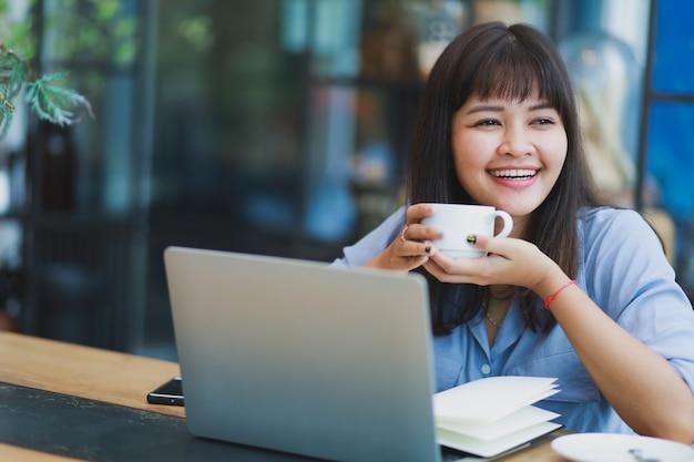 Mulher bonita asiática na camisa azul usando laptop e bebendo café Foto Premium