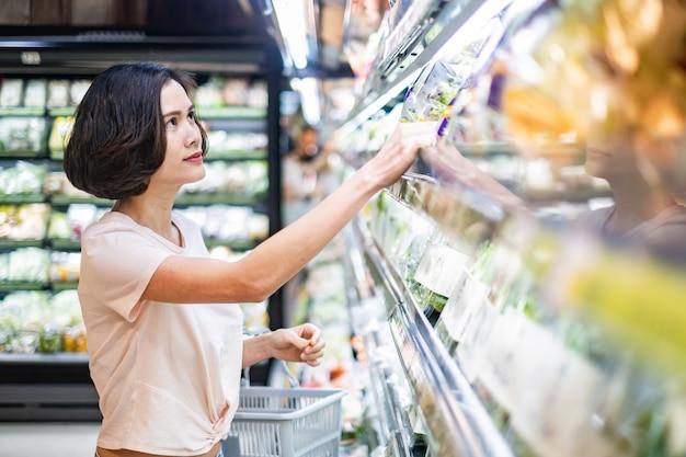Mulher bonita asiática nova que guarda a cesta do mantimento que anda no supermercado. Foto Premium