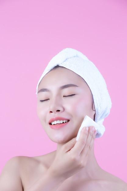 Mulher bonita asiática que limpa a cara em um fundo, em uma cosmetologia e em uns termas cor-de-rosa. Foto gratuita