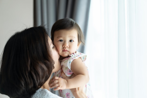 Mulher bonita asiática que prende o bebê e beijar a bochecha criança no quarto em casa. Foto Premium