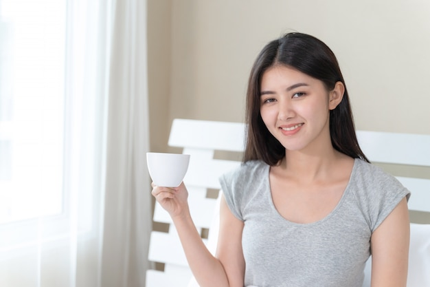 Mulher bonita asiática, sentada na cama no quarto e segurando a xícara de café na mão com feliz Foto gratuita