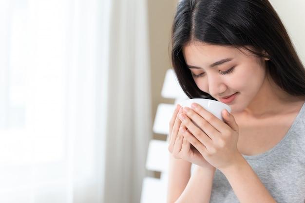 Mulher bonita asiática, sentada na cama no quarto e segurando a xícara de café na mão Foto gratuita