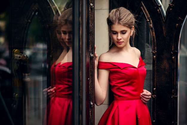 Mulher bonita atraente em um vestido vermelho de pé pela porta de metal forjado Foto Premium