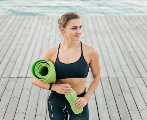 Mulher bonita caucasiana em sportswear tem um colchonete nas mãos e coloca em um terraço de praia Foto Premium