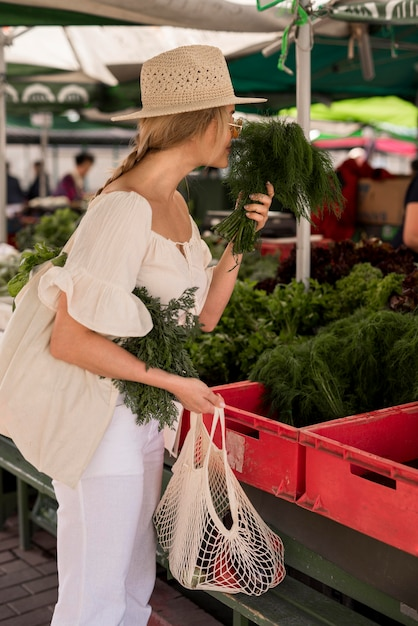 Mulher bonita cheirando folhas de endro Foto gratuita
