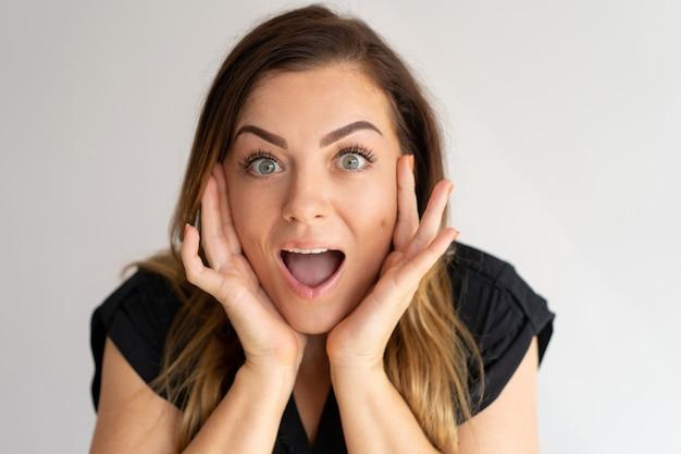 Mulher bonita chocada tocando o rosto com a boca aberta Foto gratuita