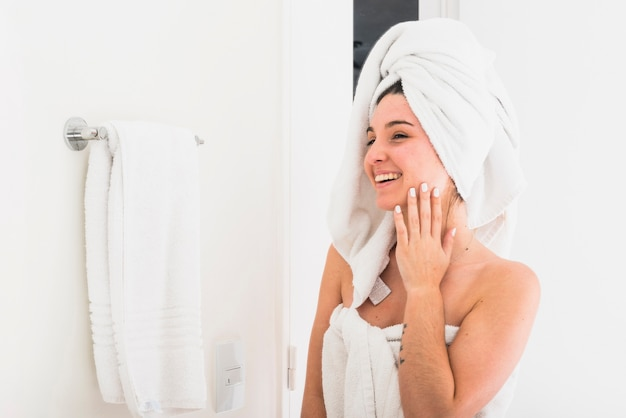 Mulher bonita com a toalha enrolada na cabeça olhando no espelho Foto gratuita