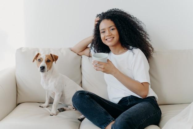 Mulher bonita com cabelo afro, bebe café, posa na sala de estar no sofá com cachorro de raça Foto Premium