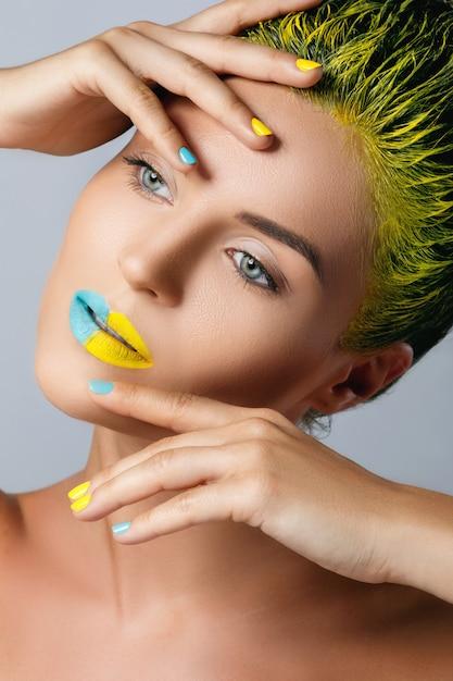 Mulher bonita com cabelo amarelo e unhas e lábios coloridos Foto Premium
