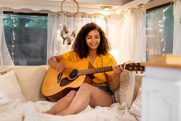 Mulher bonita com cabelo encaracolado tocando guitarra Foto gratuita