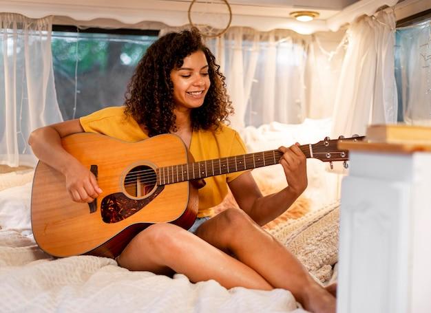 Mulher bonita com cabelo encaracolado tocando violão Foto Premium