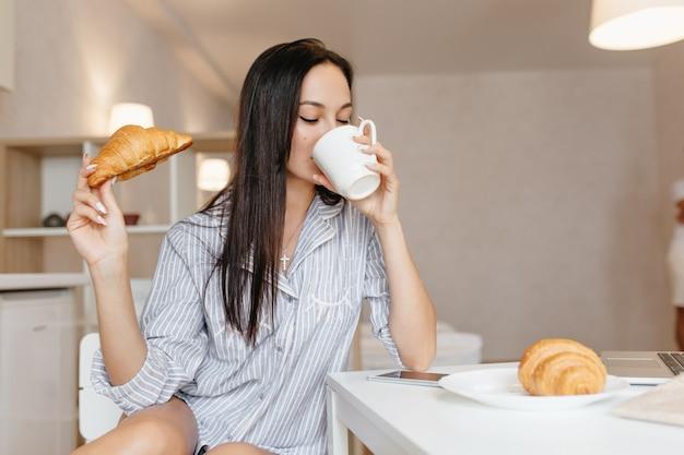 Mulher bonita com cabelo preto brilhante tomando café durante o café da manhã Foto gratuita