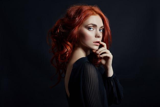 Mulher bonita com cabelo vermelho em uma parede preta. retrato de uma mulher de sucesso, pele pura, maquiagem natural, rosto de cuidados da pele. retrato de contraste de uma mulher adulta Foto Premium