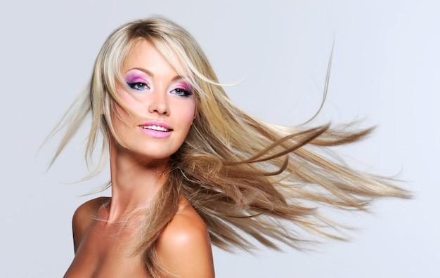 Mulher bonita com cabelos longos e lisos e maquiagem multicolorida Foto gratuita