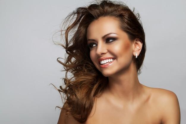 Mulher bonita com cachos e maquiagem Foto gratuita