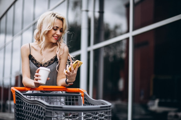Mulher bonita com carrinho de compras fora Foto gratuita