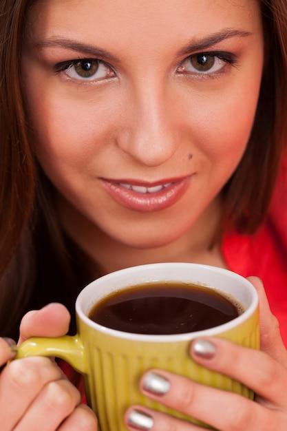Mulher bonita com copo em casa Foto gratuita