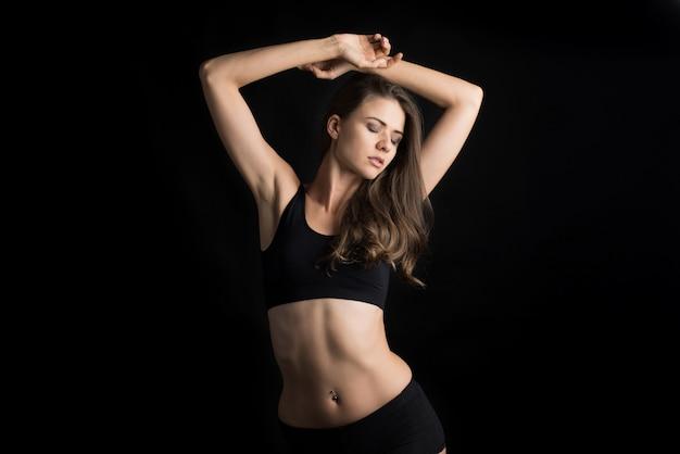 Mulher bonita com corpo saudável em fundo preto Foto gratuita