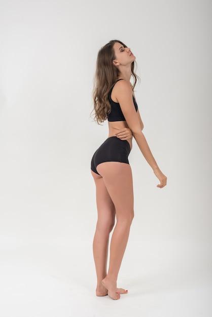 Mulher bonita com corpo saudável no fundo branco Foto gratuita