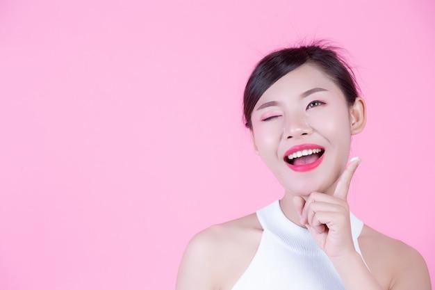 Mulher bonita com creme na pele em um fundo cor-de-rosa. Foto gratuita