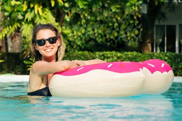 Mulher bonita com donut inflável na piscina Foto Premium