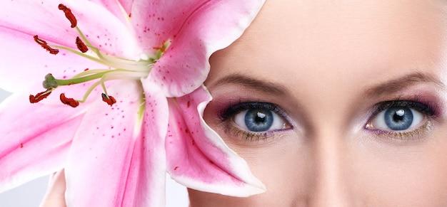 Mulher bonita com flor de lírio rosa Foto gratuita
