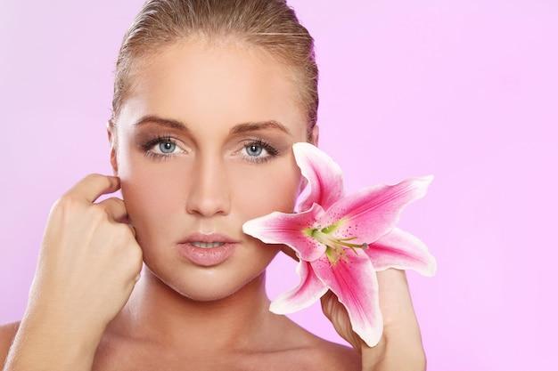 Mulher bonita com flor de lírio Foto gratuita