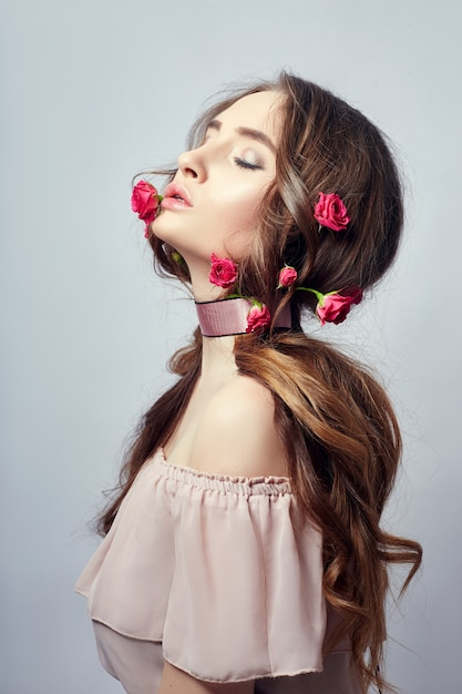 Mulher bonita com flores rosas em seus longos cabelos Foto Premium