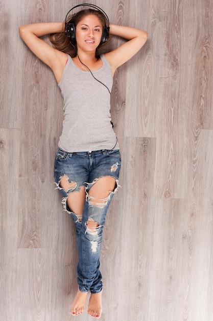 Mulher bonita com fones de ouvido deitado no chão Foto gratuita