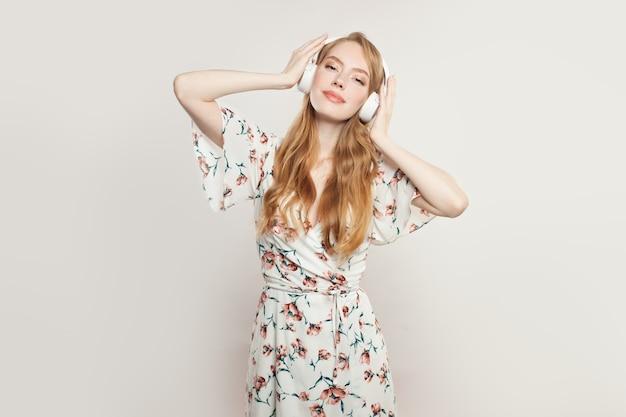 Mulher bonita com fones de ouvido. modelo ruiva ouvindo música em branco Foto Premium