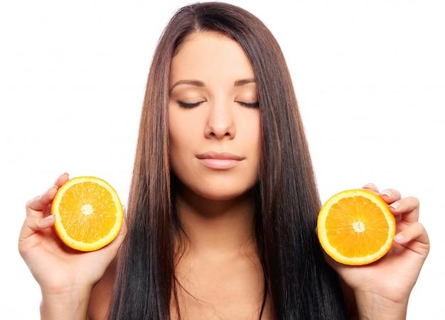 Mulher bonita com laranja nas mãos Foto gratuita