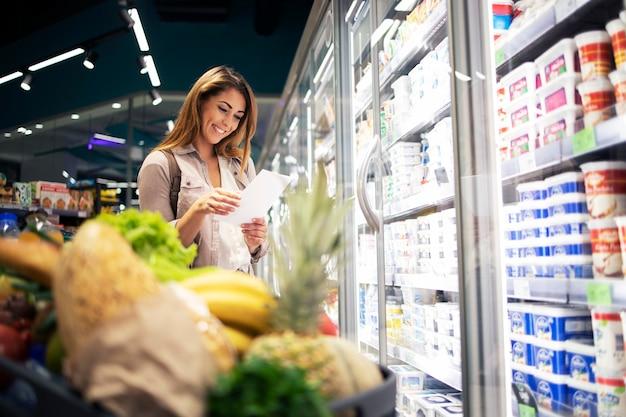 Mulher bonita com lista de compras comprando comida no supermercado Foto gratuita