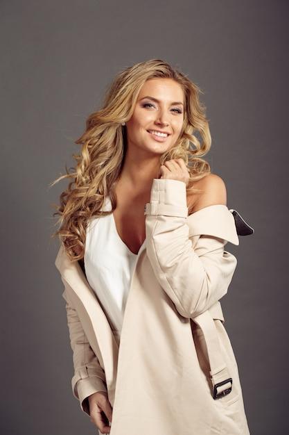 Mulher bonita, com longos cabelos loiros com casaco de pele bege Foto Premium