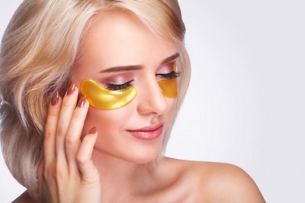 Mulher bonita com manchas de hidrogel de ouro Foto Premium