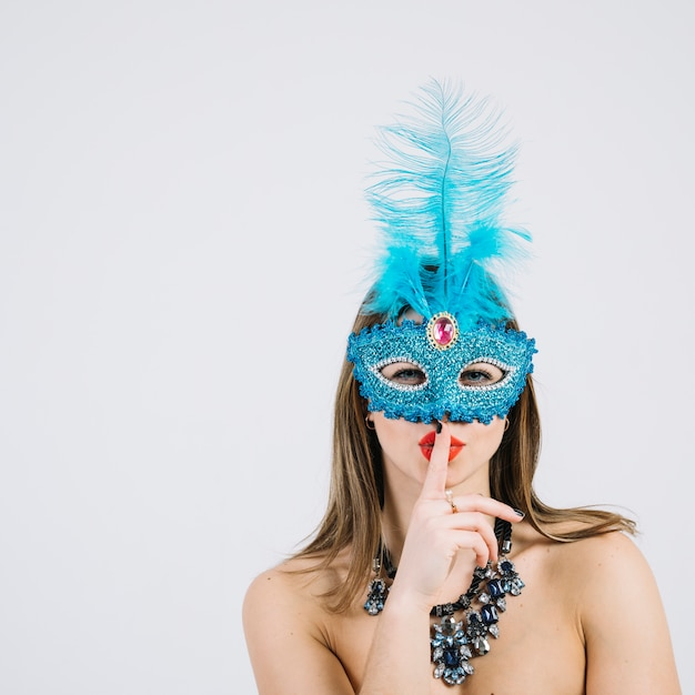 Mulher bonita com máscara de carnaval com o dedo nos lábios Foto gratuita